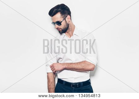Used to look perfect. Handsome young man in white shirt adjusting his sleeve while standing against white background