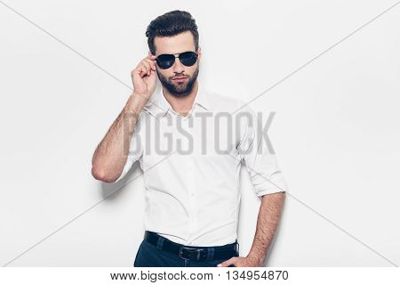 Real heartbreaker. Handsome young man in white shirt looking at camera while standing against white background