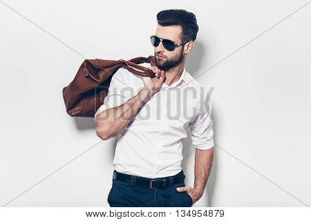 Ready to go. Handsome young man in white shirt carrying leather bag on shoulder and looking away while standing against white background