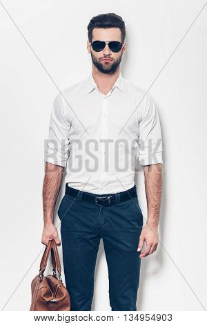 Handsome man with bag. Handsome young man in white shirt carrying leather bag and looking at camera while standing against white background