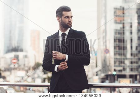 Modern businessman. Confident young man in full suit adjusting his sleeve and looking away while standing outdoors with cityscape in the background