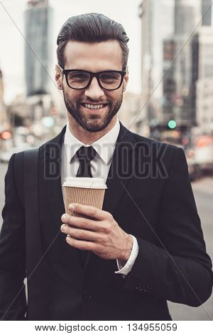 Inspired with cup of fresh coffee. Confident young man in full suit holding coffee cup and looking at camera with smile while standing outdoors with cityscape in the background