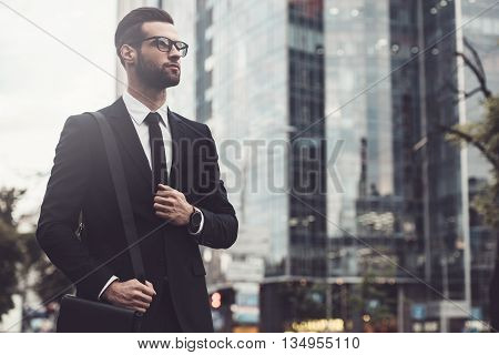 Businessman on the go. Low angle view of confident young and handsome man in full suit walking along the street with cityscape in the background