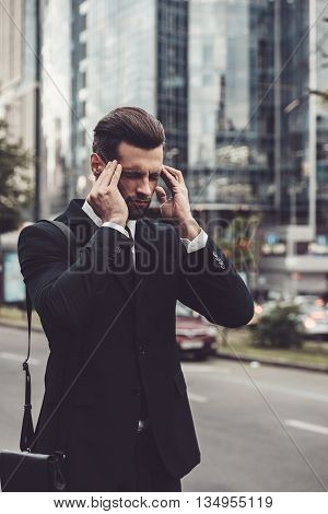 Feeling that awful headache. Frustrated young man in full suit touching his head with hands and keeping eyes closed while standing outdoors with cityscape in the background