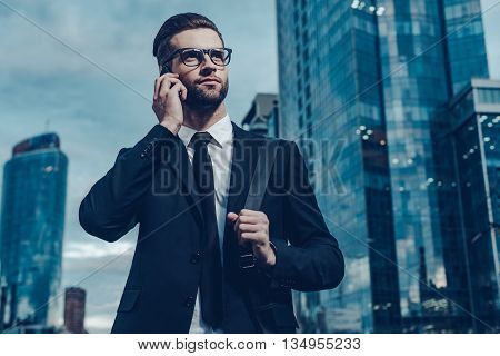 Doing business on the go. Night time image of confident young man in full suit talking on the mobile phone and looking away while standing outdoors with cityscape in the background