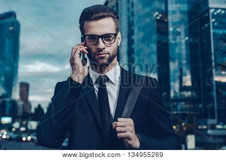 Staying in touch. Night time image of confident young man in full suit talking on the mobile phone and looking at camera while standing outdoors with cityscape in the background