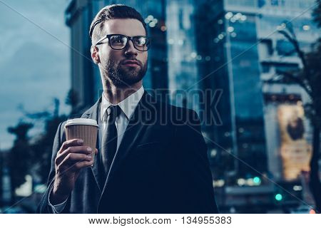 Restoring energy. Night time image of confident young man in full suit holding coffee cup and looking away while standing outdoors with cityscape in the background
