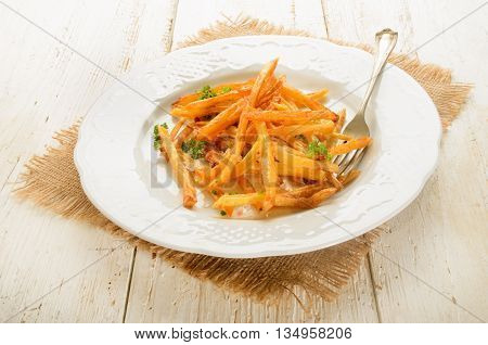 warm french fries with red pepper salt and parsley served on white plate