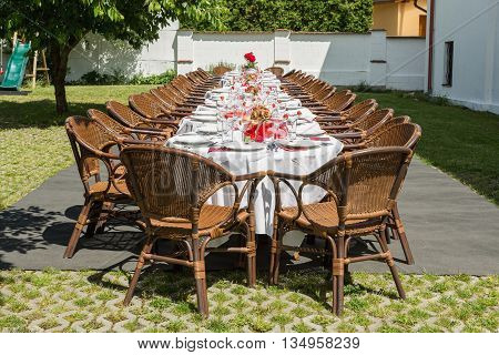 garden party set up for lunch dinner with long table Decorated table with candles in the garden