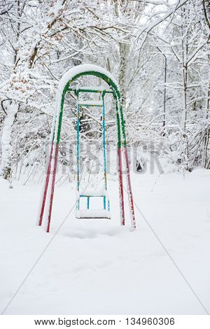 Abandoned children's swings abundantly covered with snow in winter park
