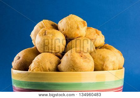 batata vada or aalu bonda or aalu bonde, a tasty indian snacks, served with tomato ketchup or green chilli and onion