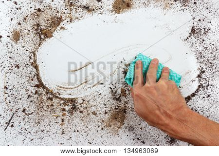 Hand with rag wiping a very dirty surface