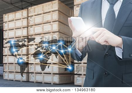 Double exposure of businessman using smart phone network connection world map , transportation port and blurred cargo warehouse background international transportation trading business concept