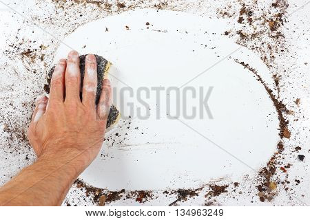 Hand with wet black sponge wiping a heavily dirty surface