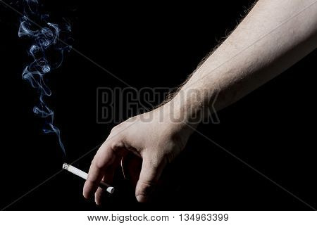 Man's Hand Holding a Smoking Cigarette on Black Background. Close up with White Cigarette Smoke