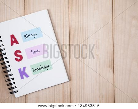 Word spell ASK and handwriting word Always Seek Knowledge on notebook with wood background