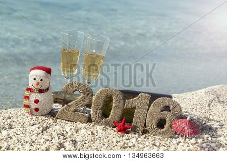 Champagne bottle lying on the beach with two champagne glasses snowman starfish and cardboard numbers 2016 placed next to it. Seascape in the background.
