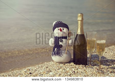 Bottle of champaign on a beach with two glasses and a snowman placed next to it sunrise in the background