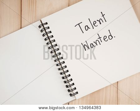 Handwriting Talent Wanted on blank notebook with wood background (Business Concept)
