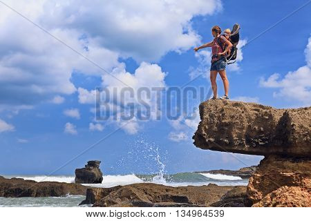 Nature walk on sea beach. Happy mother high rock cliff hold little traveller in carrying backpack. Baby ride on woman back. Travel adventure hiking with child carrier family summer vacation on Bali.