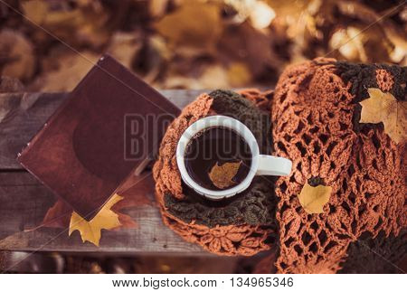 Hot coffee and red book with autumn leaves on wood background