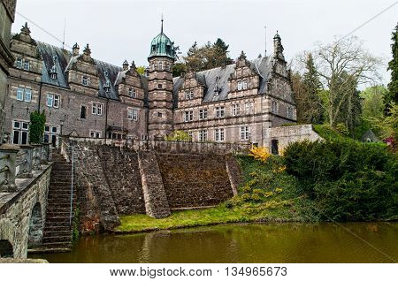 Side view on the castle Emmerthal from the garden with a lake in Lower Saxony. Germany