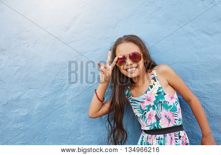 Portrait of cute little girl with sunglasses gesturing peace sign. Preteen girl standing against blue wall with copy space.