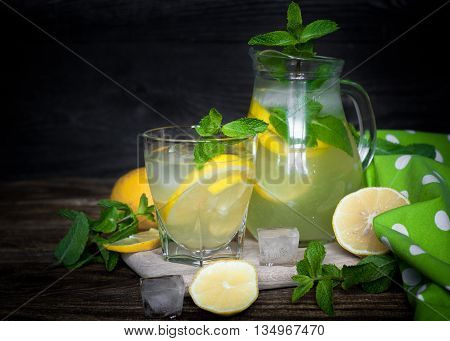 Lemonade in a glass and jug. Traditional summer drink