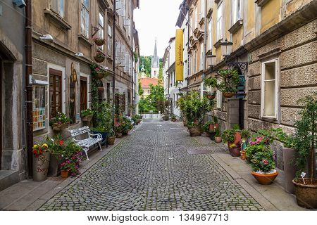 LJUBLJANA SLOVENIA - 26TH MAY 2016: A view along streets of Ljubljana during the day showing the outside of buildings and plants. A person on a bike can be seen in the distance.