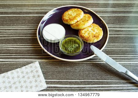 Homemade Salty Cheese Pancakes with sauce Pesto. Cheesecake pancakes with sour cream. Pancakes photographed close.