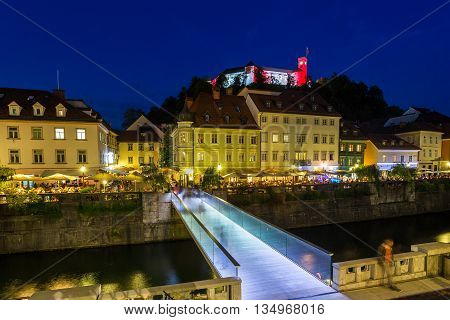 LJUBLJANA SLOVENIA - 26TH MAY 2016: A view towards Ljubljana Castle at night. A bridge buildings and people can be seen.