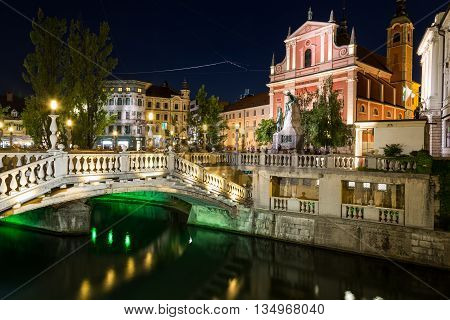 LJUBLJANA SLOVENIA - 26TH MAY 2016: Franciscan Church of the Annunciation the Triple Bridges and other buildings in Ljubljana at night