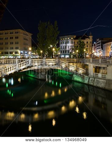 LJUBLJANA SLOVENIA - 26TH MAY 2016: Part of the Triple Bridges and other buildings in Ljubljana at night. People can be seen.