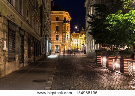 LJUBLJANA SLOVENIA - 26TH MAY 2016: A view along streets of Ljubljana at night. Buildings and the blur of people can be seen.