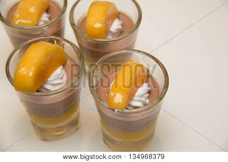 chocolate mousse in glass with cream and mango