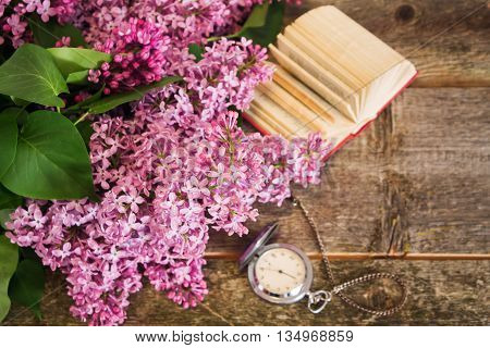 lilac branch on the background of blurred clock and books. Shallow depth of field. Focus on the center of lilac.