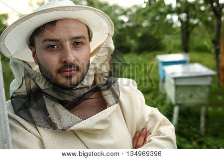 portrait of a beekeeper on apiary at hive