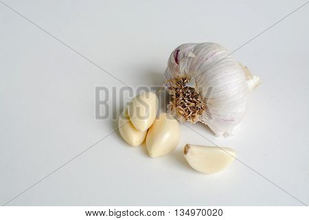Fresh peeled raw garlic cloves and a half head of garlic with skin on on white background