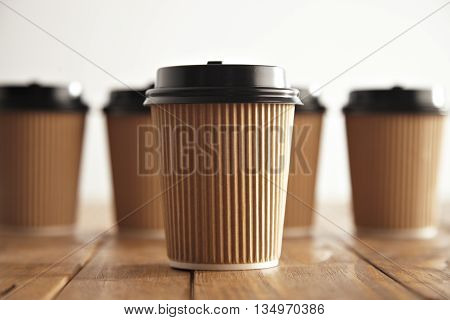 One focused craft paper coffee cup with black cap isolated in center in front of unfocused group of others on vintage brushed pallet table close view