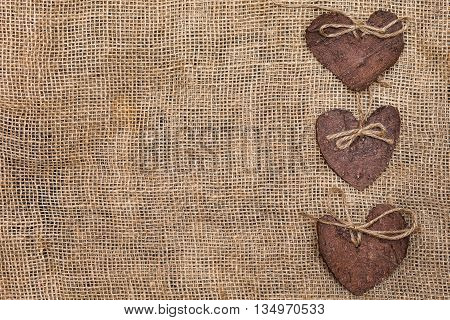 Three (3) decorative hearts made from tree bark on sackcloth, positioned on right side of the photo. Hearts decorated with eco twine. Eco decor. St. Valentines greeting card idea. Handmade design.