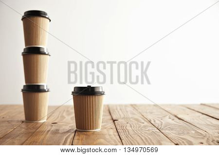 One focused cardboard paper cup in front of three take away cups with black caps standing in column on left side of rustic vintage table isolated on white