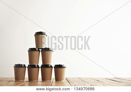 Brown cardboard take away paper cups with black caps in pyramid house shape isolated on left side of rustic vintage table