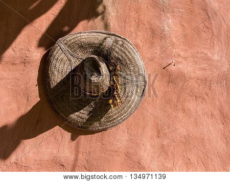 Straw hat hanging on textured clay wall