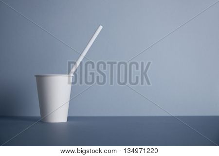 One take away white paper cup without cap with drinking straw inside presented in left side, isolated on gray