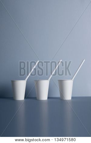 Three take away white paper cups without caps with drinking straws inside presented in center, isolated on gray
