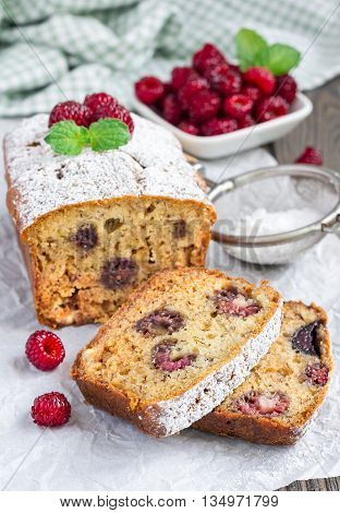 Sliced banana bread with raspberries cherries and white chocolate on parchment