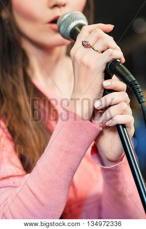 Closeup of singing caucasian woman. Young unrecognizable woman emotionally sings into the microphone, holding it with two hands.
