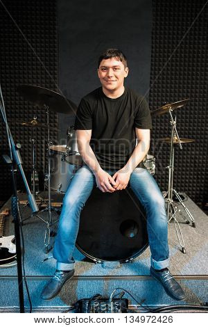 Smiling drummer sitting on the drum. Guy sitting on big drum smiles at camera. Young smiling drummer in casual clothes at music studio