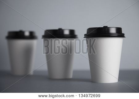 Three take away white paper cups with closed black caps, top view, isolated on simple gray background, first cup in close focus, cups behind are unfocused in bokeh