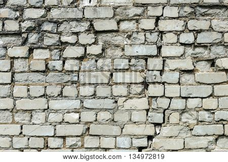 Background of old cracked white brick wall